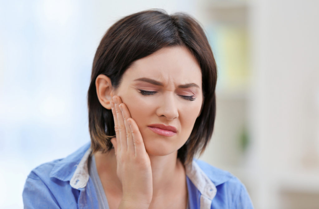Woman rubbing her jaw because she has TMD.