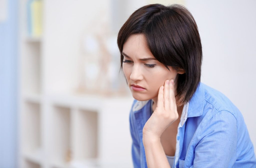 Woman touching her jaw because of bruxism pain