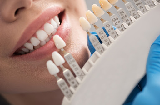 Smiling dental patient next to row of ceramic crowns