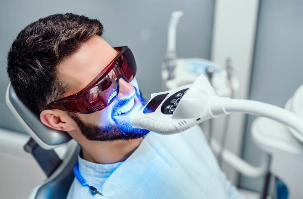 Smiling man having teeth whitened with light in dental office